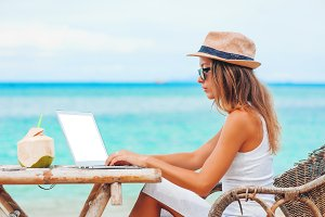 Young woman using laptop on the beach. Freelance work
