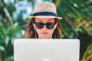 Young woman freelancer working in laptop on the beach. Freelance work