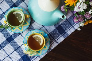 Cups of herbal tea with chamomile and mint leaves on the wooden background
