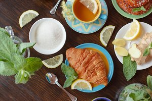 Cup of herbal tea with lemon and mint leaves, ginger root and croissant on the wooden background