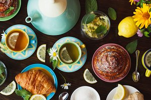 Cups of herbal tea with lemon and mint leaves, ginger root and croissant on the wooden background