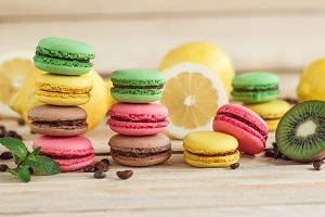 Green, pink, yellow and brown french macarons with lemon and coffee beans