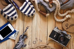 Striped slippers, camera, phone and miniature of the statue of liberty on the wooden background