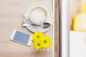 Cup of cappuccino, phone and bouquet of yellow flowers, wooden table