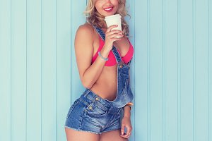 Young sexy woman drinking holding take away coffee cup toned instagram filter