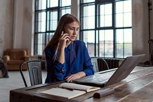 Businessman talking on the phone while working on laptop sitting at her desk in stylish modern office