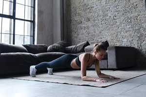 Fit young woman wearing sportswear working out at home doing planking exercise on carpet