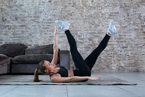 Sportswoman training at home. Fit female athlete doing toe touch single arm exercise lying on floor in loft apartment