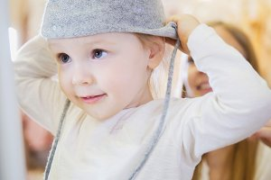 The little girl in front of a mirror wearing a grey beanie.