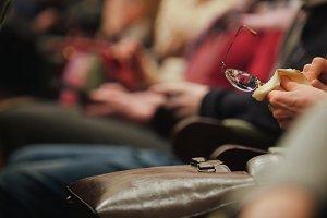 Woman rubs glasses i n concert hall