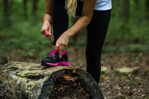 sporty girl in the woods, tying the laces on sports shoes
