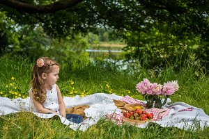 little girl resting on picnic with strawberries