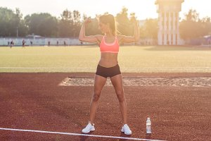 Fitness woman on stadium showing off muscular arms flexing biceps.
