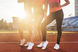 Beautiful legs of three athlete fit women at stadium.