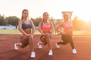 Young fit women stretching legs outdoors doing forward lunge