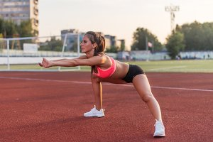 Fitness woman doing a warm-up before her training cardio workout.