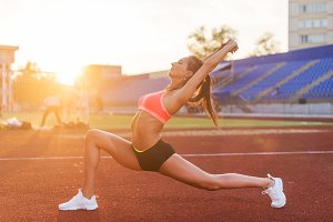Fit woman in warrior pose stretching in stadium.