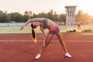 Fit woman warming up in stadium, bending and stretching her back leg muscles