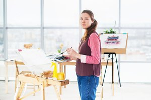 Portrait of a young woman painter drawing with watercolor palette on paper using easel.