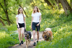 Two teenage girls walking with her dogs in park