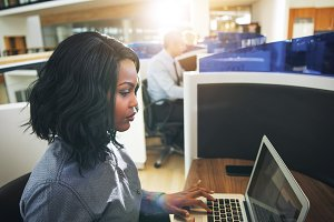 Young black woman typing laptop at workplace in office