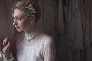 Thoughtful young bride looking through window