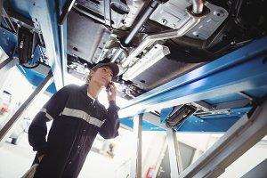 Female mechanic talking on mobile phone under a car