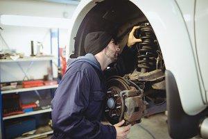 Mechanic examining a car wheel disc brake