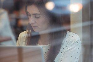 Businesswoman using laptop at café table