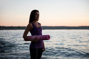 Beautiful woman standing with exercise mat on beach
