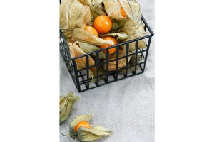 Close-up of Physalis fruit in a black basket