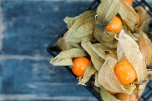 Top view on Physalis fruit in a black basket