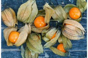 Top view on Physalis fruit on a old blue rustic board.