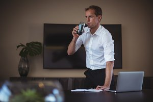 Businessman having water while working in office
