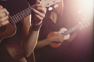 Women playing a guitar in music school