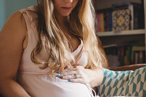 Pregnant woman relaxing in living room
