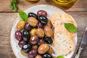 Olive oil, different olive fruites and fresh bread.