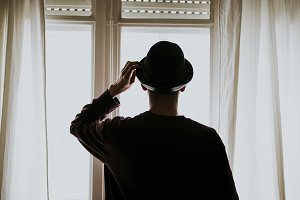 young man with Hat looking out the window of the room backlit