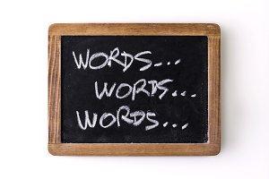 """""""Words"""" written 3 times on a slate"""