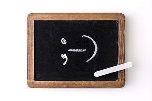Icon &#x3B;-) (wink) written on a slate