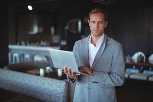 Businessman standing with a laptop