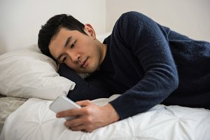 Man using mobile phone on bed