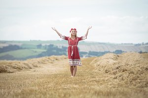 Blonde woman standing in field with her arms spread
