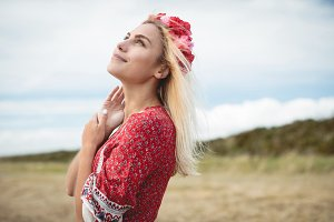 Blonde woman wearing a flower tiara standing in field