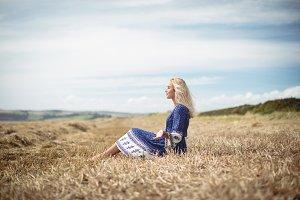 Blonde woman sitting in field