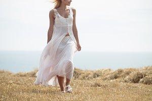 Blonde woman walking in field near a river