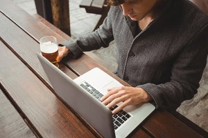 Man using laptop while having glass of beer