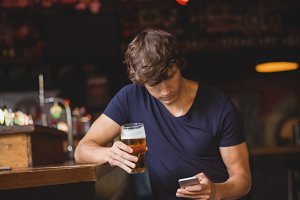 Man using mobile phone while having glass of beer