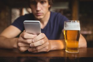 Man using mobile phone with beer glass on table