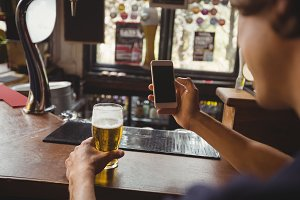 Man with glass of beer using mobile phone in counter